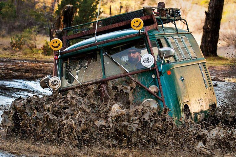 Green camper van driving through mud