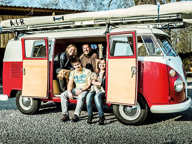 Red and white camper van with family and dogs sitting inside