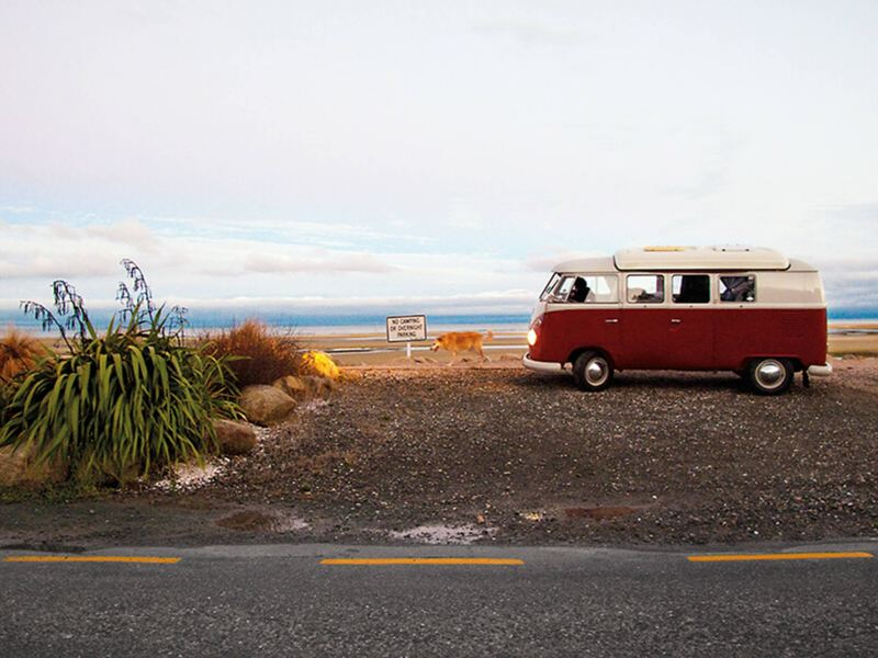 Red and white camper van on the beach with dog