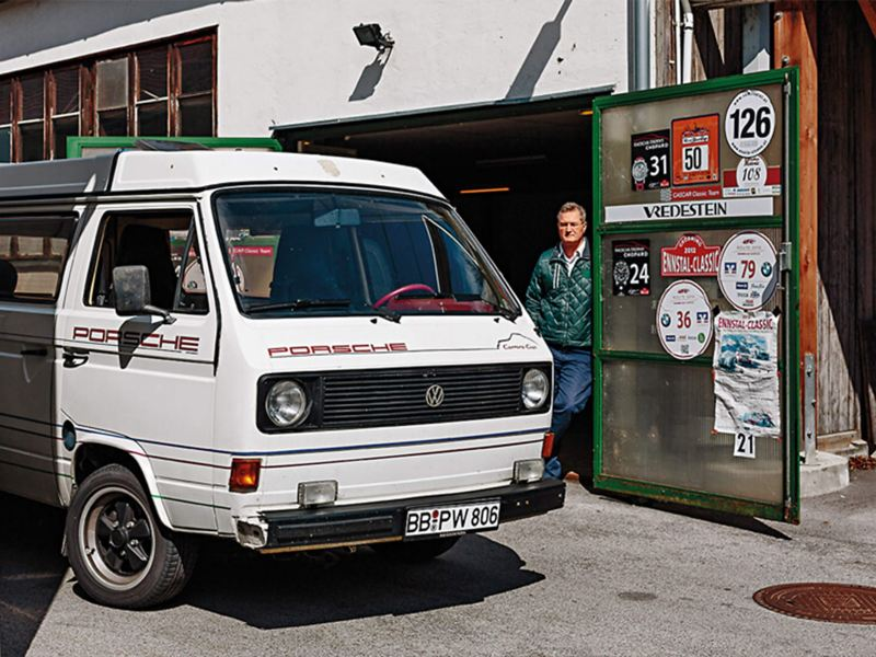 Man standing by Porsche camper van