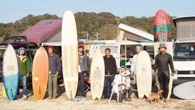 Men on beach with surfboards standing in front of camper vans