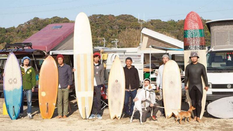 Men on beach with surfboards standing in front of camper vans