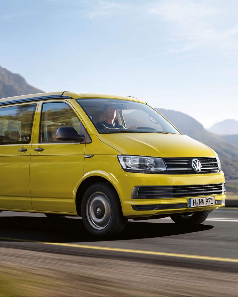 Yellow VW California camper van on mountain road