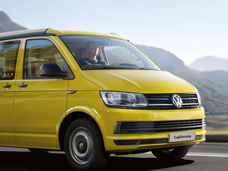 Yellow VW California camper van on mountain road