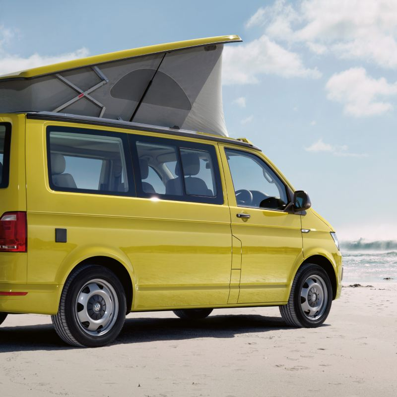 Yellow california van on the beach with surfers