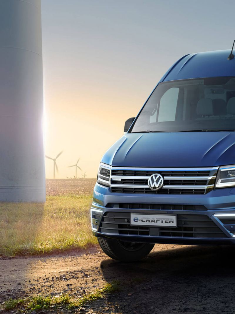 Blue VW e-Crafter front view with a grassy field and wind turbines in the background