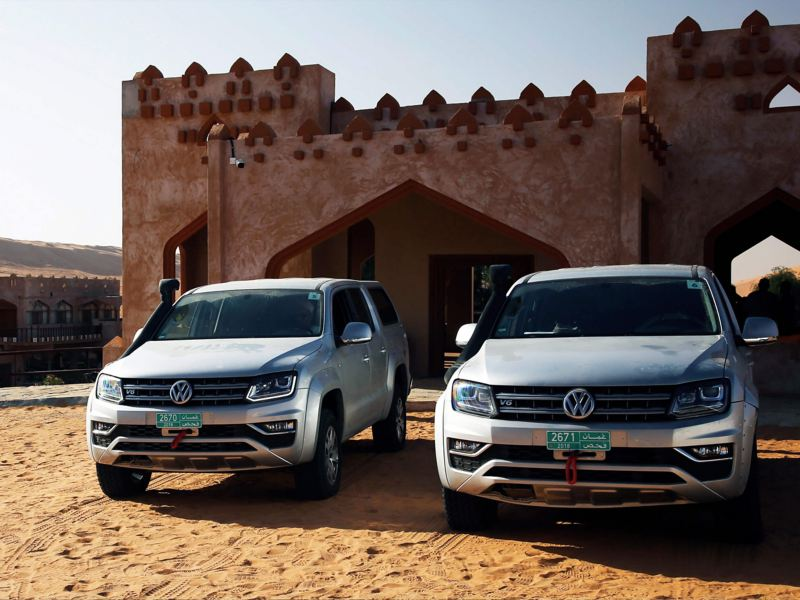 Two grey Amarok front view next to a middle-eastern style building