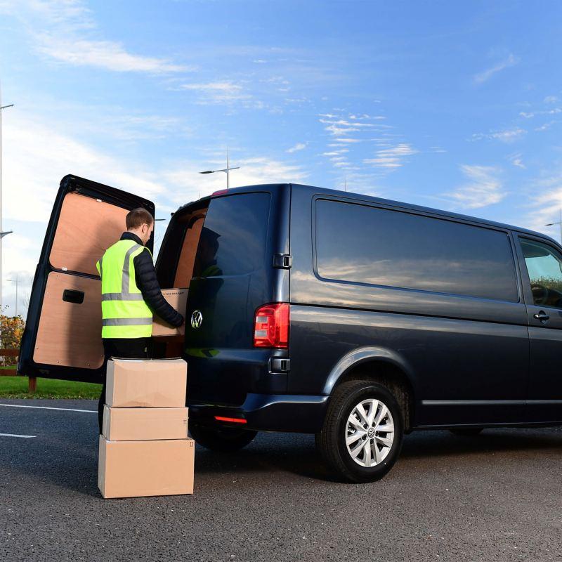 Van driver loading boxes into a van
