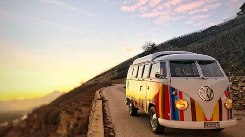 Stripey campervan driving on road with sunset background