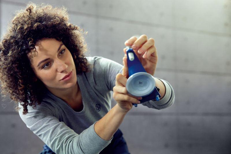 Eine Mechanikerin repariert eine Windschutzscheibe.