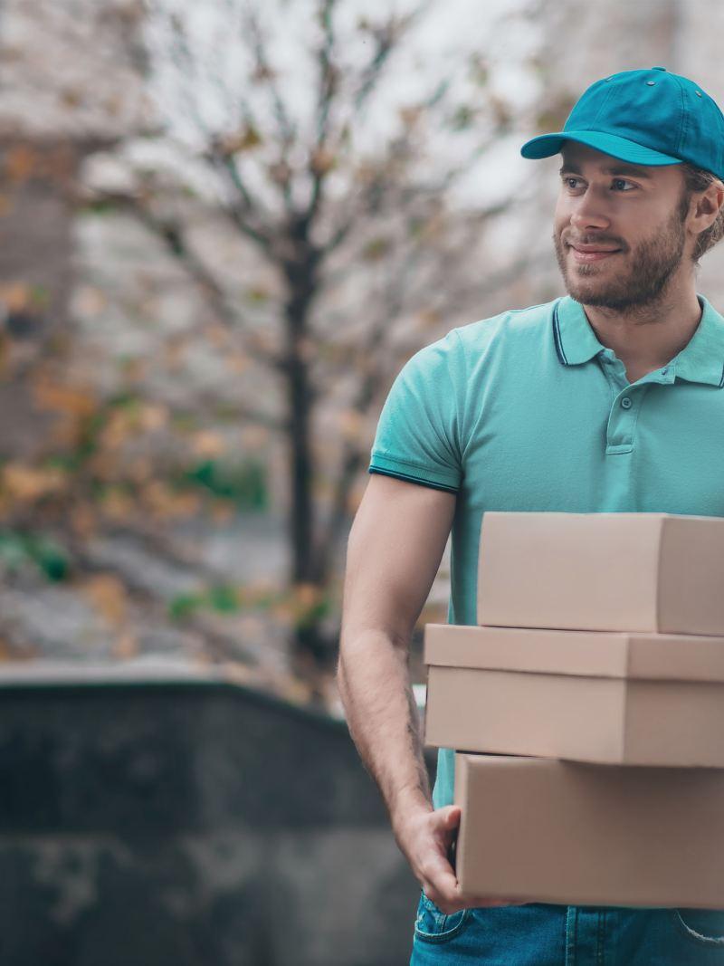 Ein Paket Kurier trägt Päckchen.