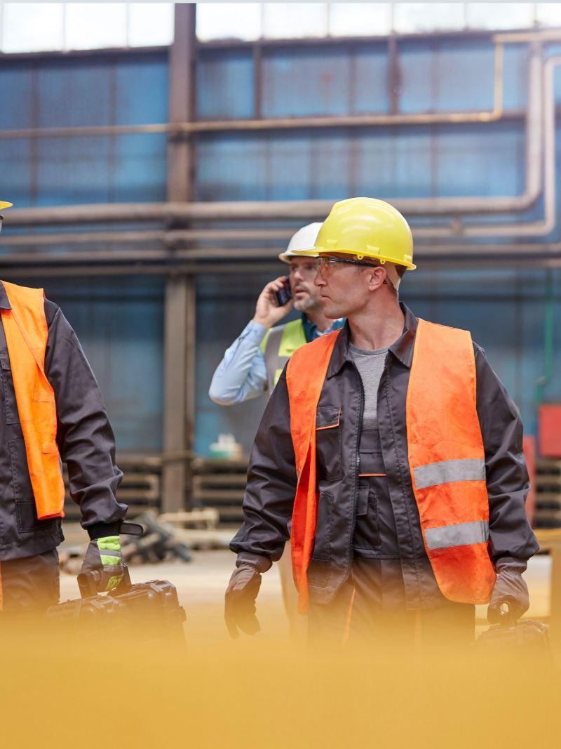 Drei Bauarbeiter auf einer Baustelle.