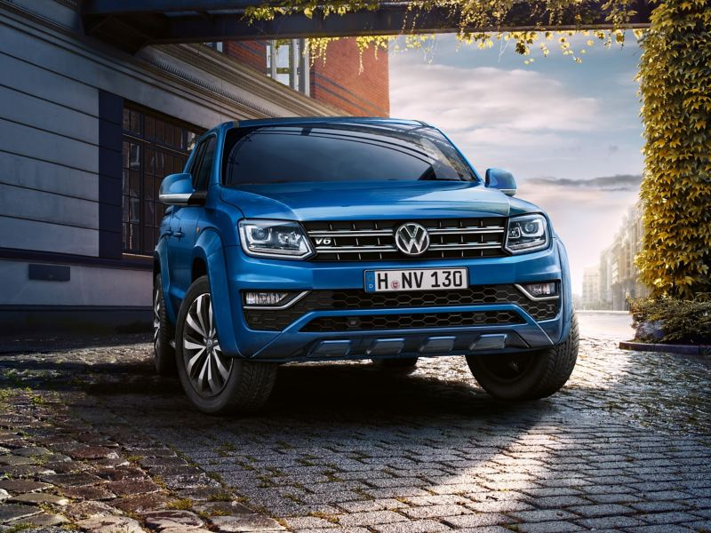 A blue VW Amarok with a striking design against an urban backdrop.