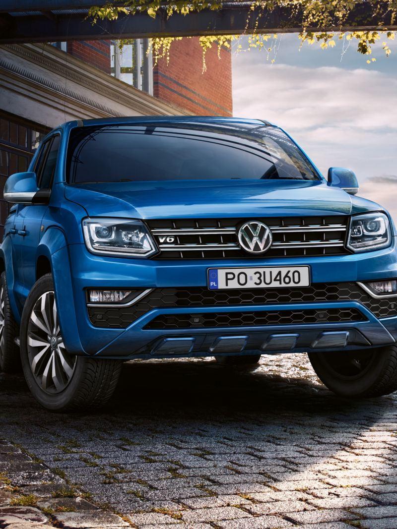 Niebieski Volkswagen Amarok z charakterystycznym designem w miejskim otoczeniu.