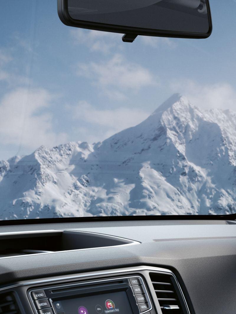 Ein Blick auf schneebedeckte Berge durch eine Windschutzscheibe.