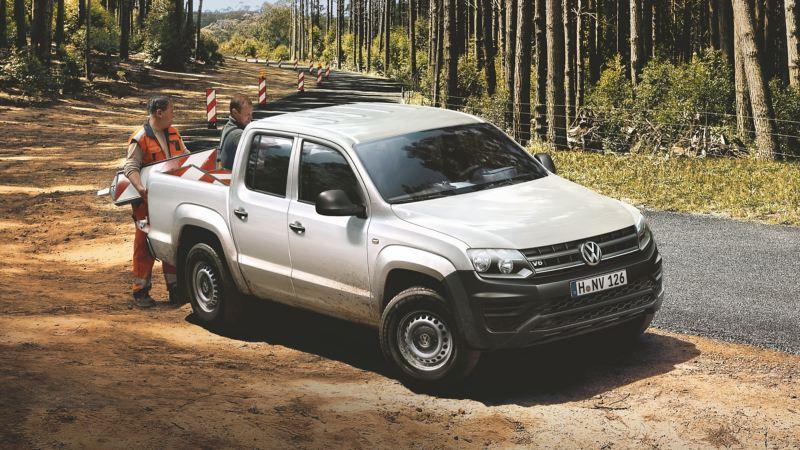 Volkswagen Amarok parkissa tien sivussa maalaistiellä, kaksi työmiestä lastaa auton lavalle tavaraa