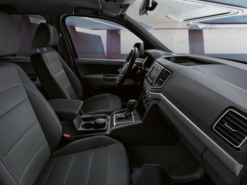"""Widok z boku do wnętrza kabiny z fotelami kierowcy i pasażera z tapicerką """"Salipra"""" w kolorze tytanowym czarnym."""