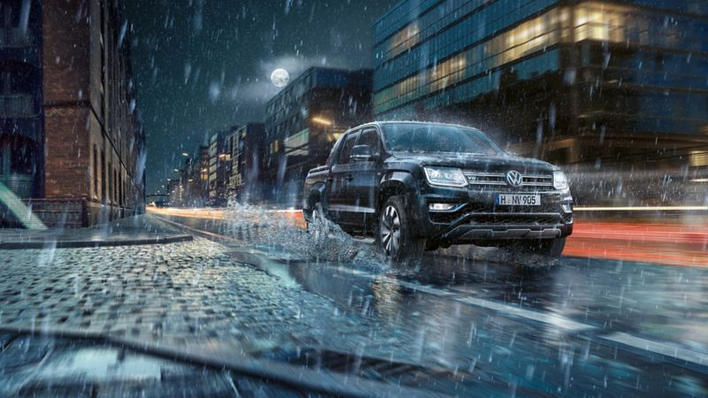The VW Amarok is driving dynamically through a rainy city at night. Water sprays out to the side.