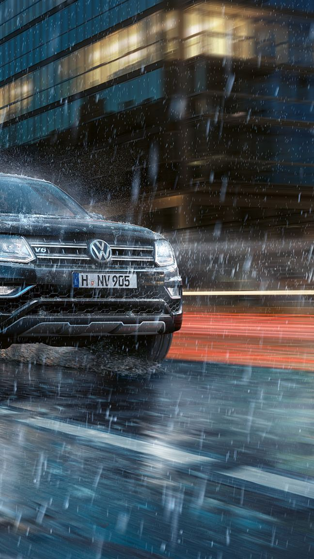 The Amarok drives dynamically through a city at night in the rain. Water splashes to the side.