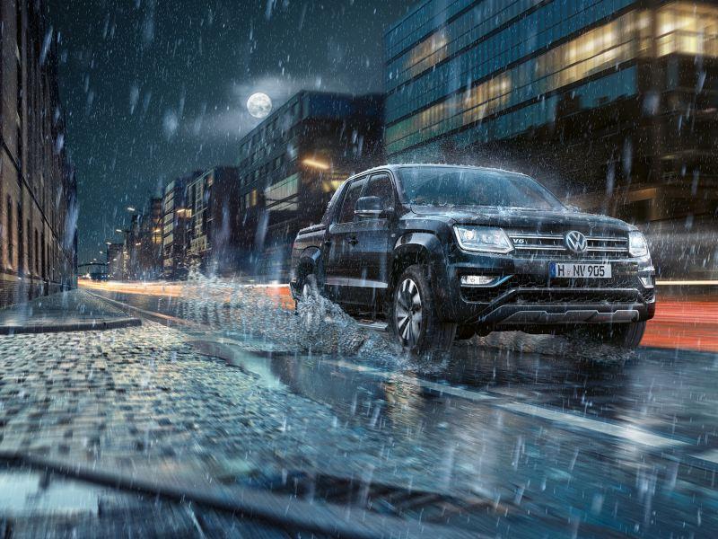 Der Amarok fährt nachts im Regen dynamisch durch eine Stadt. Wasser spritzt zur Seite.