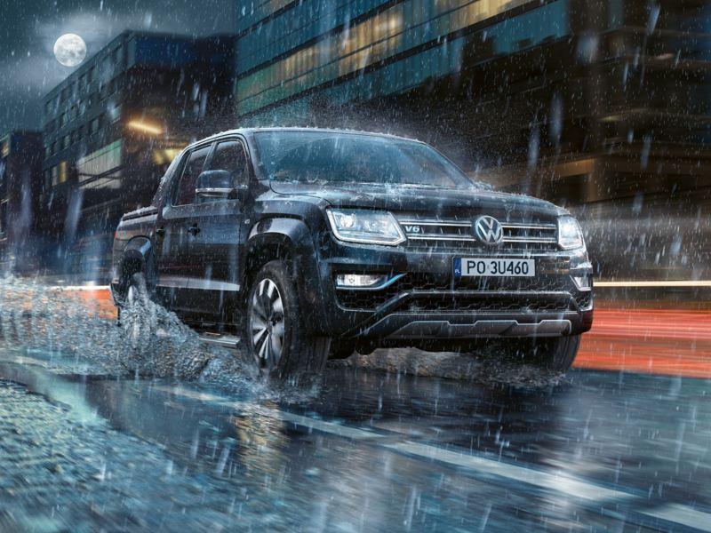 Amarok dynamicznie przejeżdża nocą przez miasto w deszczu. Woda rozpryskuje się na boki.