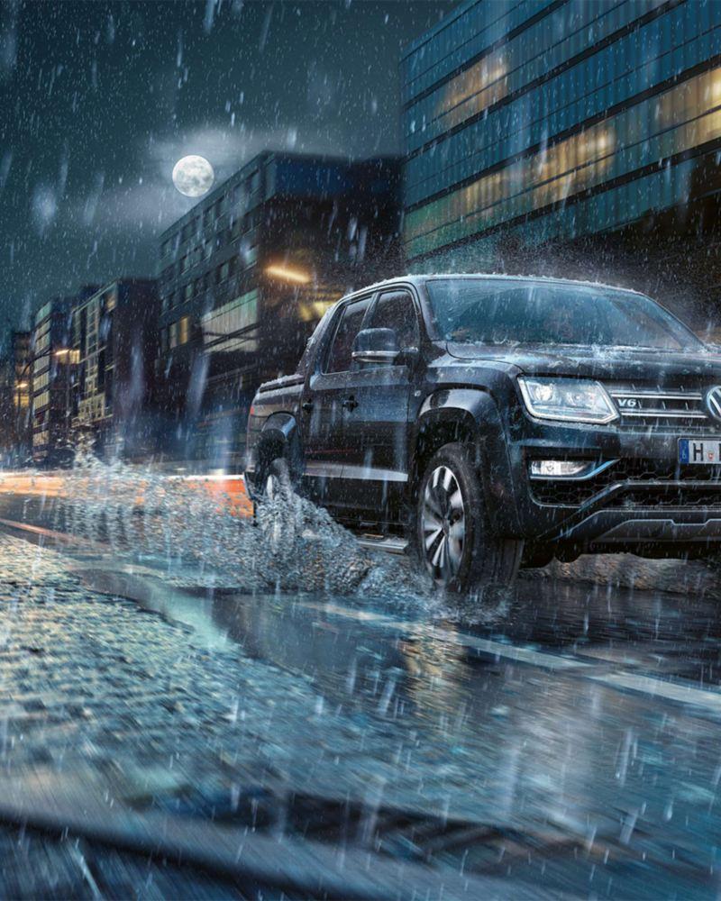 Amarok fährt in der Nacht im Regen durch die Stadt. 3/4 Frontansicht