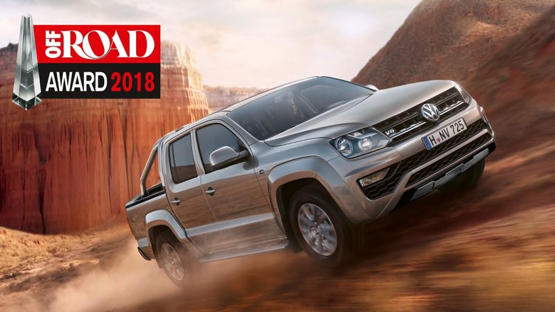 The VW Amarok drives dynamically across a dusty track. The logo for the 2018 OFFROAD AWARD is visible on the image.