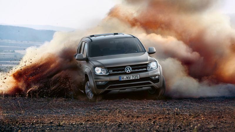 Vista frontale di Amarok Volkswagen su una strada sterrata mentre solleva una nube di polvere.
