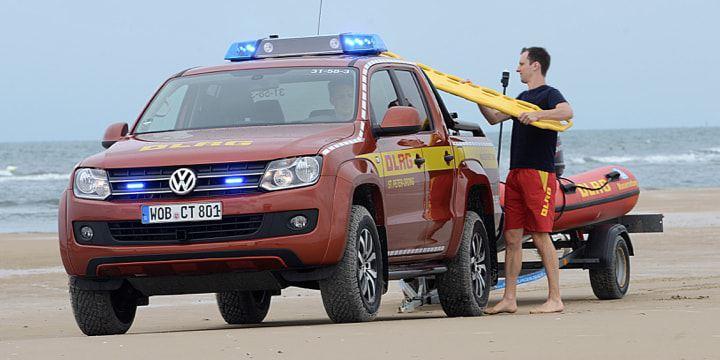 Ein Seenotretter lädt Rettungswerkzeug auf einen Amarok.