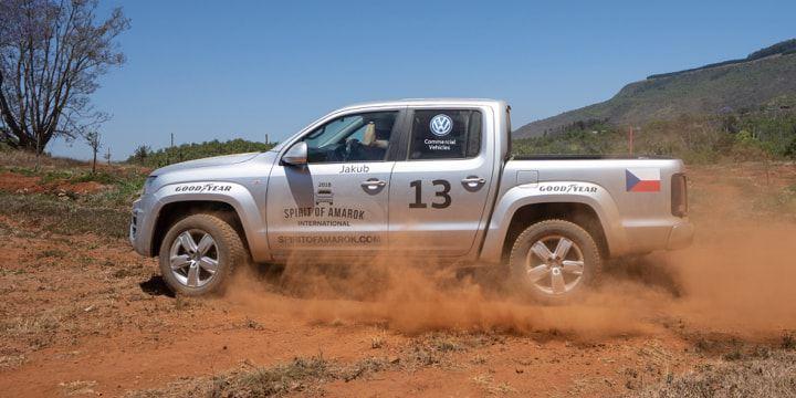 Ein Amarok durchquert die südafrikanische Wüste. Roter Staub wirbelt auf.