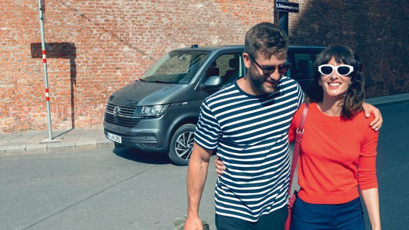 Ein junges Paar steht vor einem Caravelle 6.1.