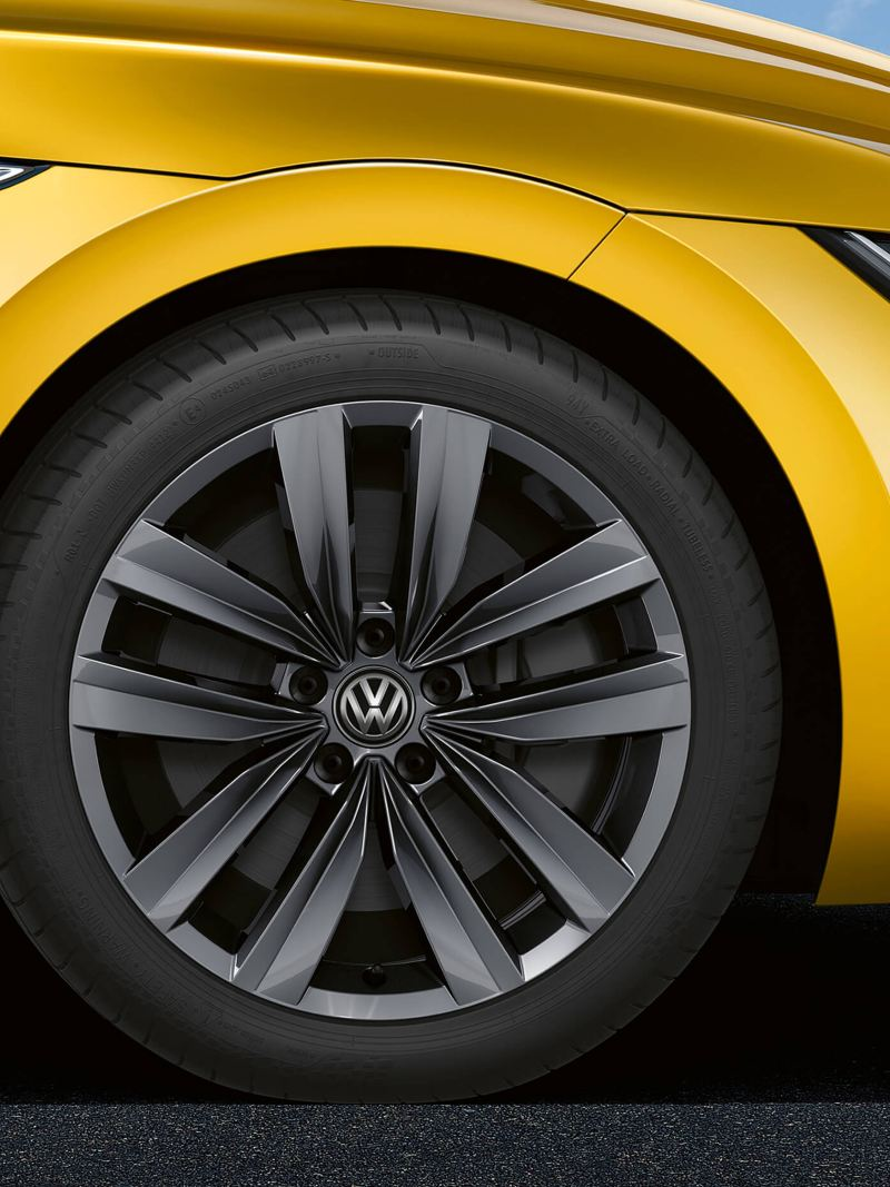 A front wheel profile shot of a yellow Volkswagen Arteon.