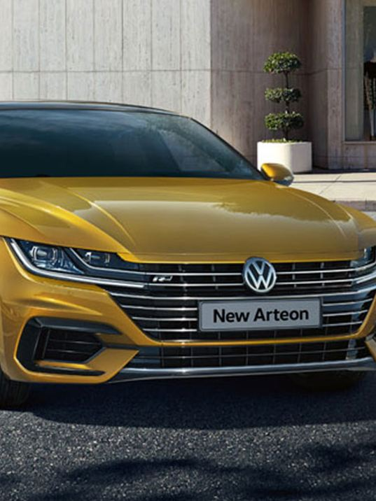 Man walks next to a parking VW Arteon