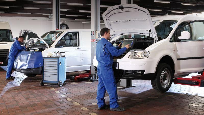 Pracownik serwisu umieszcza akumulator w komorze silnika.