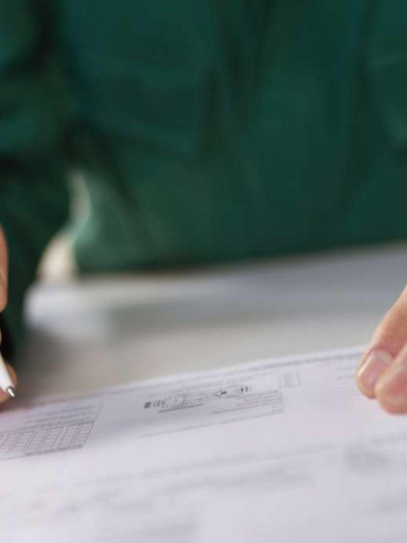 Henkilö kirjoittaa pöydällä olevaan sopimukseen