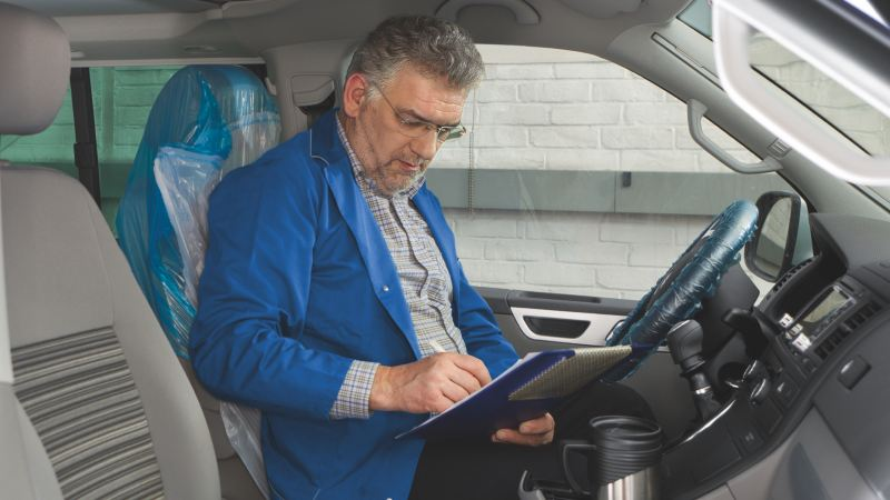 Ein Mann sitzt in einem Fahrzeug und füllt einen Prüfbogen aus.