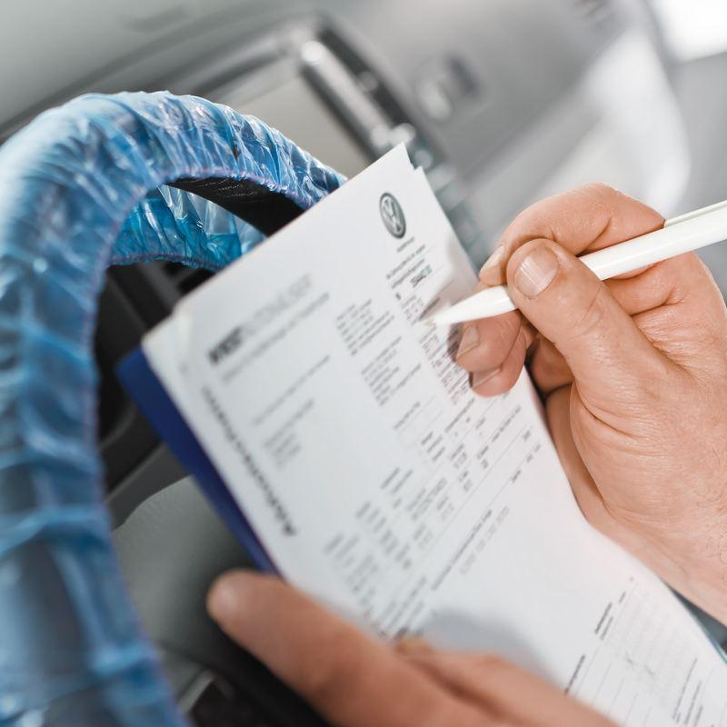 Eine Hand mit einem Kugelschreiber ist im Begriff auf ein bedrucktes Blatt Papier zu schreiben.