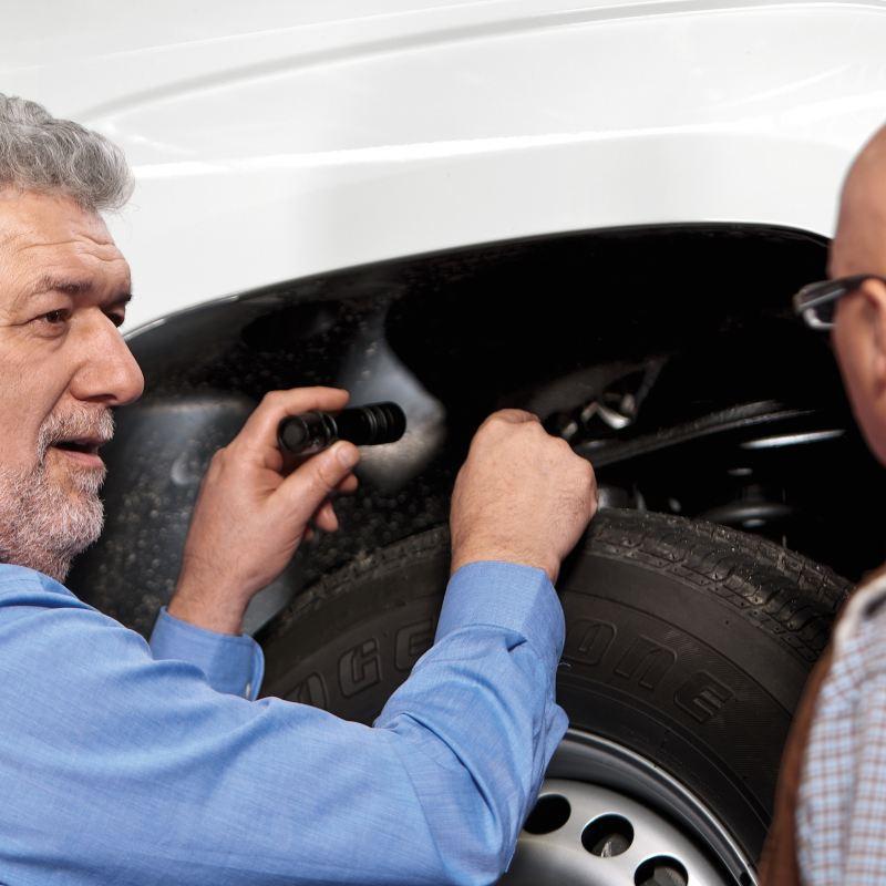 Partner Serwisowy Volkswagena z klientem oświetla latarką nadkole samochodu dostawczego.