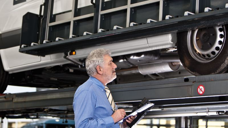 Un mécanicien contrôle le soubassement d'un véhicule.