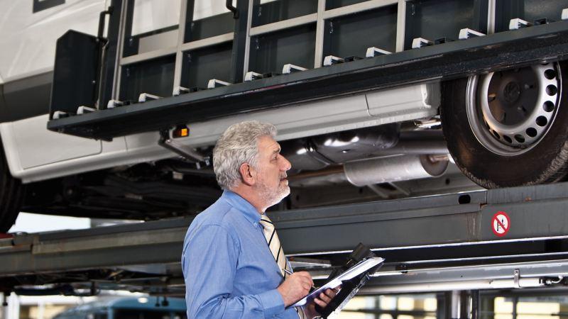 En mekaniker undersöker en VW transportbil