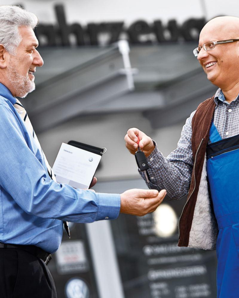 Ein Mann übergibt einem anderen Mann mit Klemmbrett Autoschlüssel.