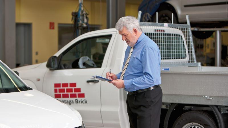 Ein älterer Mann steht zwischen Fahrzeugen und schreibt auf einen Block in seiner Hand.