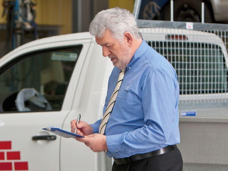 Ein Mann schreibt auf einem Clipboard.