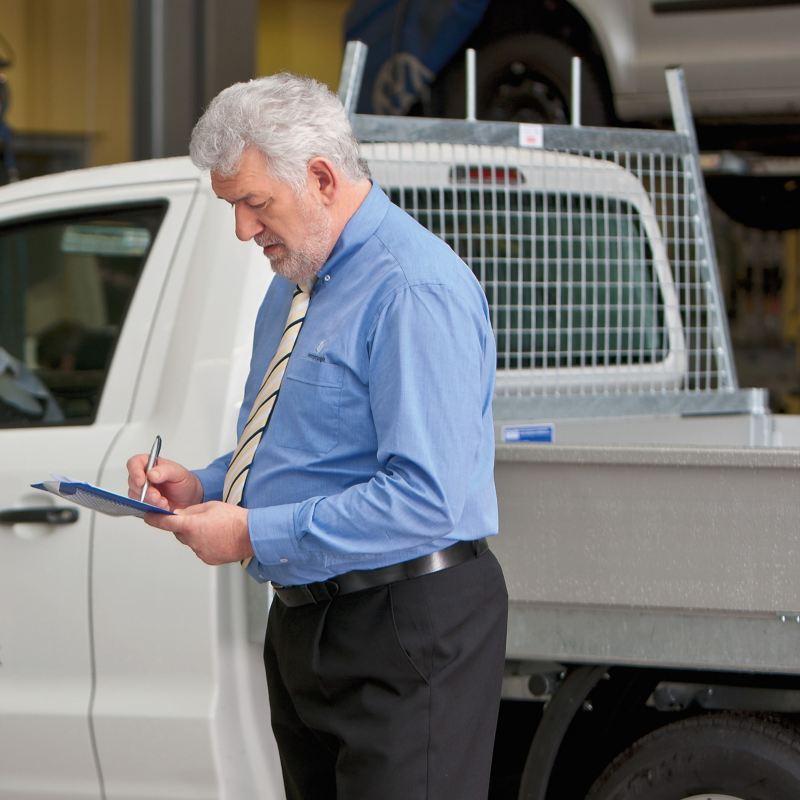 Ein älterer Herr mit Klemmbrett steht neben einem Nutzfahrzeug.