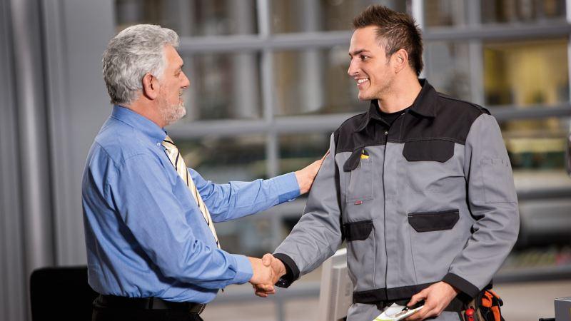 Ein Verkäufer und ein Kunde geben sich die Hand.