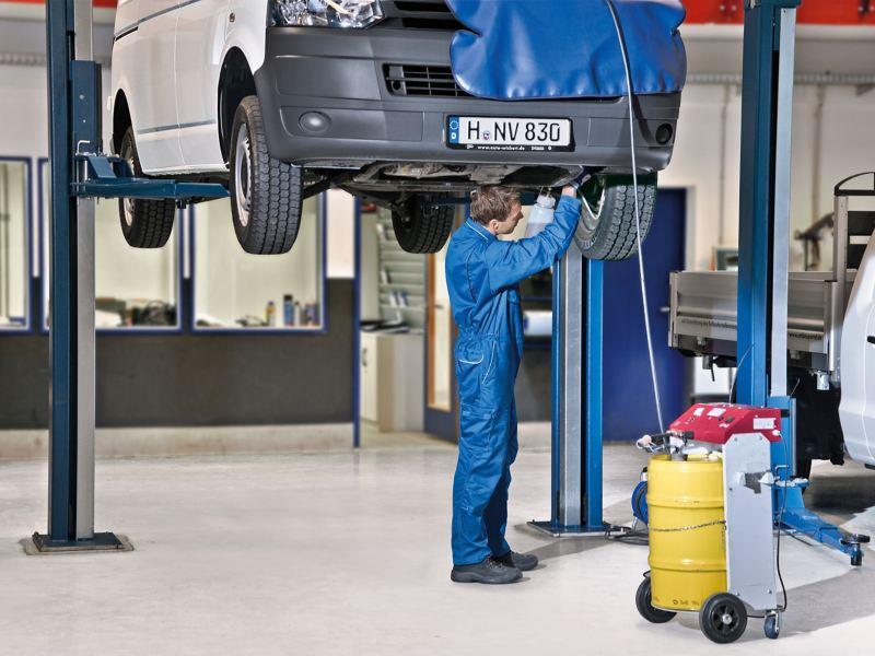 Ein Service Plus Mitarbeiter wechselt die Bremsflüssigkeit an einem Volkswagen Nutzfahrzeug.
