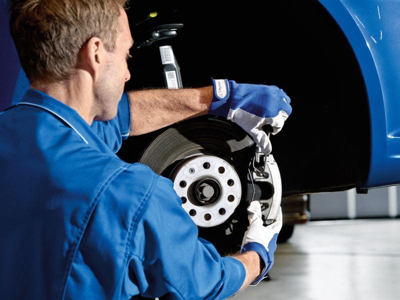 Ein Service Plus Mechaniker bearbeitet die Bremsbeläge eines Volkswagen Nutzfahrzeuges.