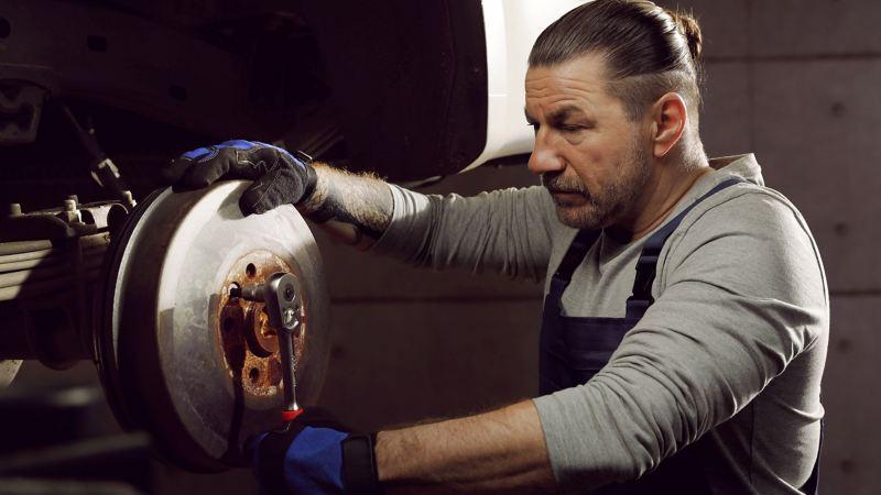 Mekaniker byter bromsklossar på en VW transportbil