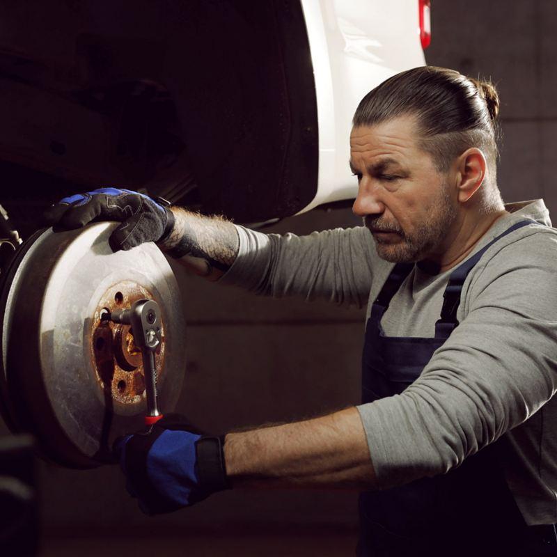 Mekaniker reparerar bromsarna på en Volkswagen transportbil
