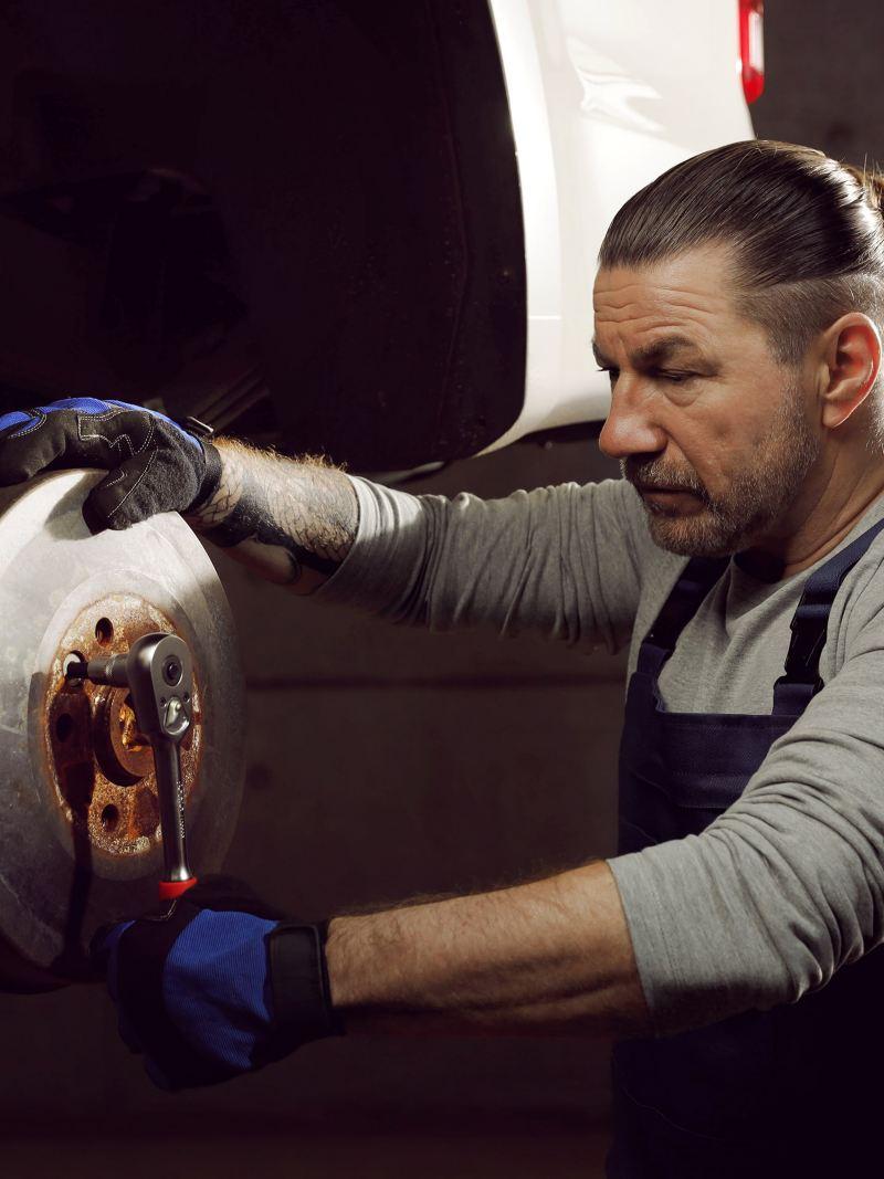 Ein Mechaniker arbeitet an einer Bremsscheibe.